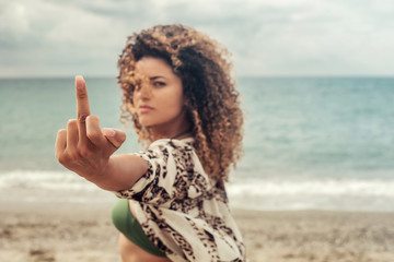 Beautiful and angry woman portrait giving the finger