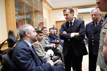 French President Emmanuel Macron meets with patients as Invalides Governor general Christophe de Saint Chamas and the director of the INI, general medical inspector Christian Plotton, listen, during a visit in Par