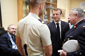 French President Emmanuel Macron meets with patients as the director of the INI, general medical  inspector Christian Plotton listens, during a visit at the Institution nationale des Invalides in Paris