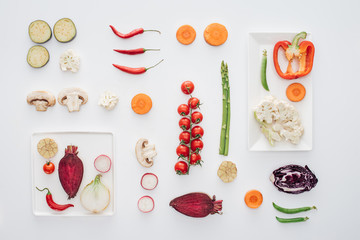 Aluminium Prints Grill / Barbecue top view of white plates and fresh sliced organic vegetables isolated on white