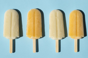 Lemon and milk popsicles on a turquoise background. Flat lay of summer sweets in pop-art style