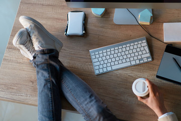 Creative web designer woman making break while holding legs on the desk.