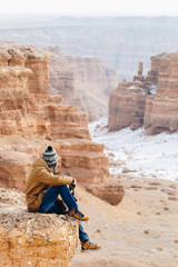 A cheerful traveler with a camera sits on the edge of a cliff in the Charyn canyon in Kazakhstan. Analogue of the American Grand Canyon.