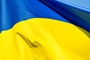 Flag of Ukraine which waving in the wind on sunny day, background, close-up