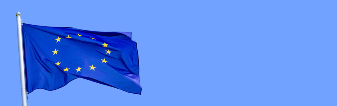 Flag of the European Union waving in the wind on flagpole against the sky on sunny day, banner, close-up
