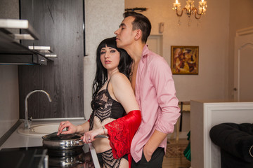 Elegant sexy couple in a black kitchen. Human vices: lust, desire, sex