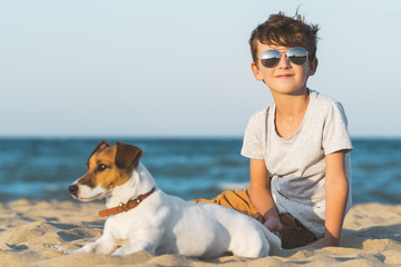 Happy boy hugging his dog breed Jack russell at the seashore against a blue sky close up at sunset. Best friends rest and have fun on vacation, play in the sand against the sea