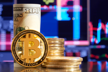 Golden bitcoin are stacked on a bright background of business graphs close-up. Bitcoin cryptocurrency. Folded in a tube 100 dollar bills. BTC