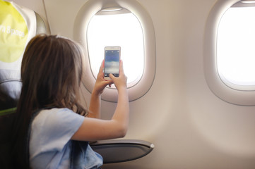 The girl sits in salon the plane on passenger sitting.