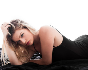 Blonde beautiful woman portrait lying on sheets and posing