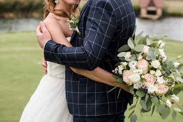 Happy bride and groom hugging near water on green golf course outdoors, copy space. Wedding couple in love, newlyweds. Wedding concept, bridal bouquet. Groom hugging bride