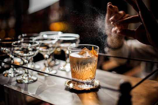 Bartender decorating fresh old fashioned summer cocktail with ice and orange peel