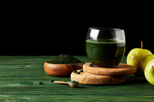 selective focus of wooden slices with fresh spirulina drink in glass, apples, wooden spoon and spirulina powder in wooden bowl on black background on black background