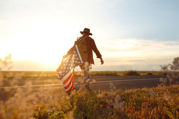4th of July. American Flag.Patriotic holiday. Traveler with the flag of America. The man is wearing a hat, a backpack, a shirt and jeans. Beautiful sunset light. American style.