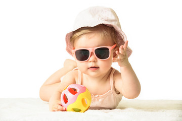 Studio portrait of adorable baby girl wearing pink plastic sunglasses, isolated on the white background, summer vacation concept