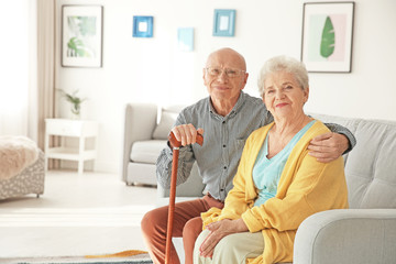 Elderly couple sitting on couch in living room