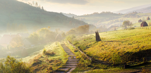 panorama of mountainous rural area on a hazy morning. beautiful landscape of Carpathians. haystacks on the grassy hillside. wooden fence along the footpath