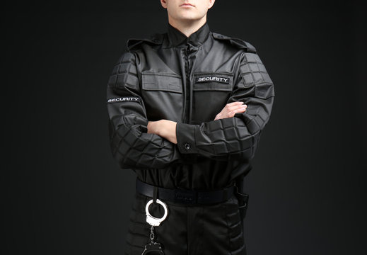 Male security guard in uniform on dark background