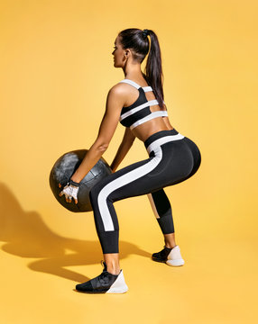 Sporty girl doing exercise with med ball for buttocks.  Photo of latin woman in fashionable sportswear on yellow background. Strength and motivation. Back view