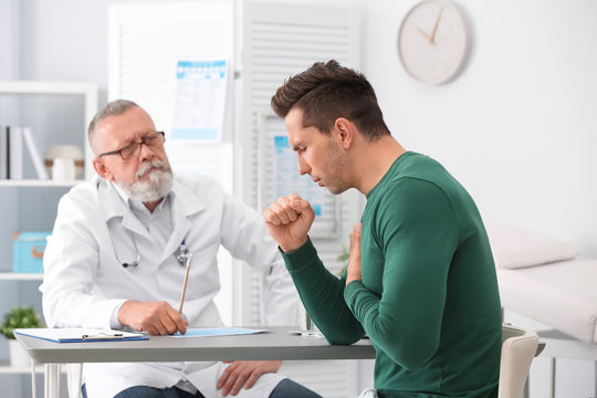 Coughing young man visiting doctor at clinic