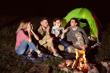 Woman with flashlight telling scary story for her friends near bonfire at night. Camping season