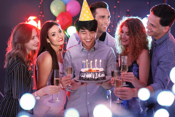 Young people celebrating birthday with cake in nightclub
