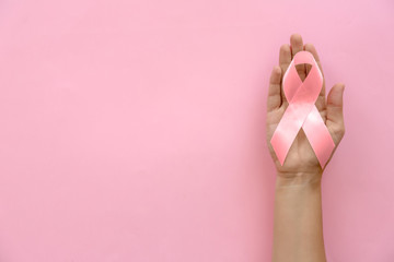 Woman holding symbolic ribbon of breast cancer awareness on color background, top view. Gynecological care