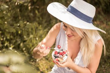Frau isst Joghurt mit Früchte