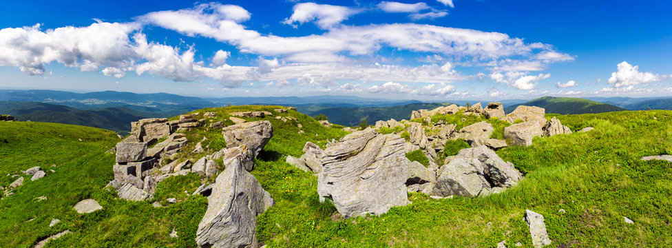 rocks of Runa mountain. panoramic view. wonderful cloudscape on a blue sky over the distant mountain range. breathtaking view of mountainous summer landscape in Carpathians