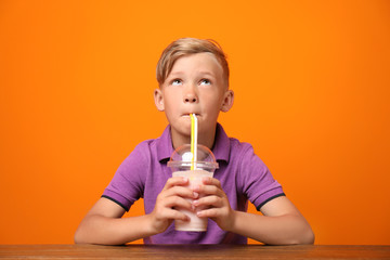 Little boy with cup of milk shake at table on color background