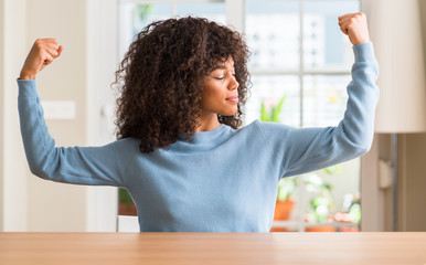 African american woman at home showing arms muscles smiling proud. Fitness concept.