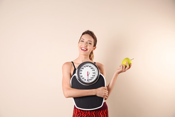Young beautiful woman with scales and apple on light background. Weight loss motivation