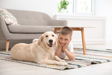 Cute little child with his pet on floor at home