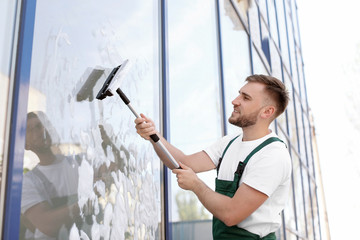 Fototapeta Male cleaner wiping window glass with squeegee from outside obraz
