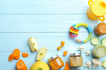 Flat lay composition with baby food and ingredients on wooden background