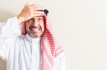 Senior arabic man stressed with hand on head, shocked with shame and surprise face, angry and frustrated. Fear and upset for mistake.