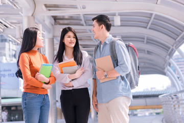 Front view of three asian students walking and talking in an university campus.