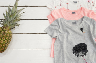 Three Shirts, Pineapple, Pink Flamingo Print. White Old Wooden Background