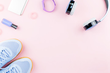 Woman sneakers, headphones, fitness tracker and smartphone on pastel pink background. Sport fashion concept. Flat lay