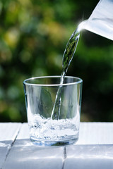 A glass filled with clean drinking water. Water is poured into a glass, a natural green floral background.