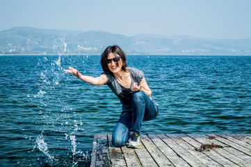 Beautiful young woman happily splashing the lake water with her hand on a wooden pier