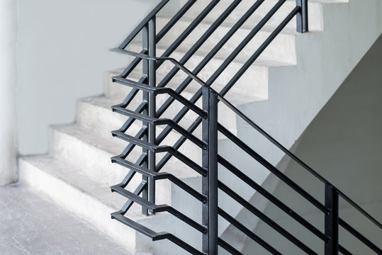 Stairway with black metallic banister in a new modern building architecture