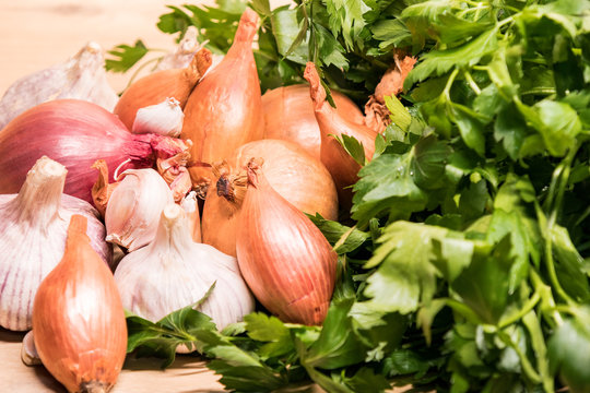 garlic onion shallot parsley on a wooden board