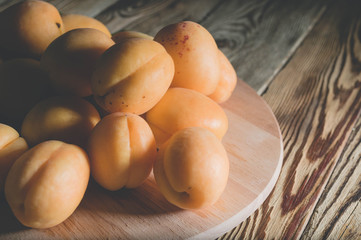 Apricots on a wooden background. Summer healthy fruits. Low key lighting