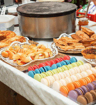 A table with variation of French style sweet and salty pastry. Croissants, macarons, Quiche Lorraine, bread with tomato and mozzarella. French style summer garden party. Farmers street food market.