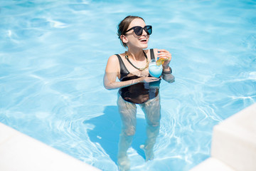 Beautiful woman in black swimsuit and sunglasses swimming with cocktail in the water pool outdoors