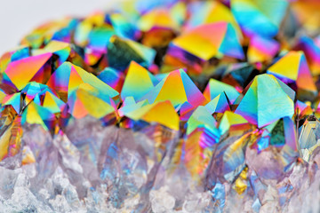 Amazing colorful flashing Amethyst Quartz Rainbow Titanium Aura Crystal cluster closeup with shallow depth of field isolated on white background. Macro of beautiful rare sparkly rainbow mineral stone