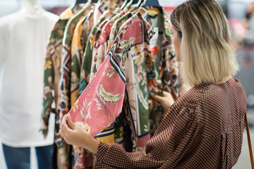 Young woman choosing clothes in mall or clothing store - Shopping, fashion, style and people concept
