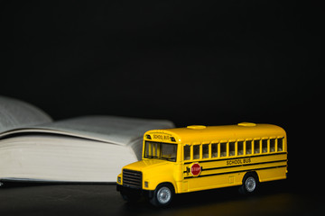 toy yellow school bus in front of a book on black background