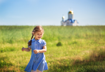 little girl in a dress runs across the field on a sunny day